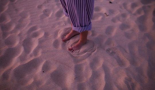 Pair of feet and bottom of stripey pants, standing in sand at dusk