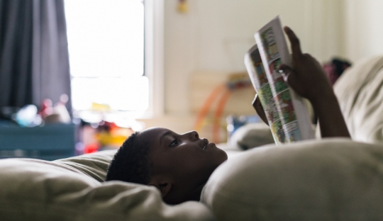 boy reading at. home lying on a bed with a window behind