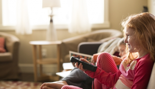 child on couch in living room watching tv