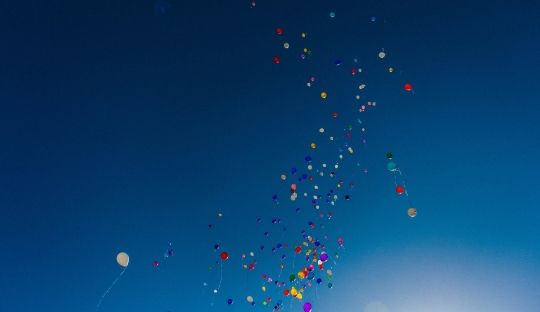 multi coloured balloons floating across a bright blue sky